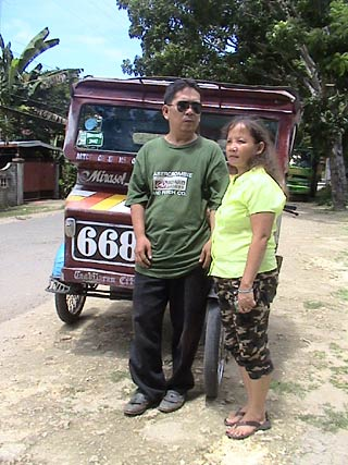 Nong Lumi and his wife Laureana standing in front of his tricycle.